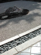 The beauty of racked gravel, smooth stone textures in dappled sun light in Japan